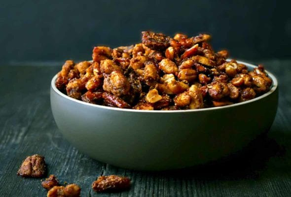 Roasted mixed nuts coated with sugar and spices in green bowl