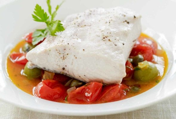 White bowl fill wth mahi mahi stewed with cherry tomatoes and capers in a broth