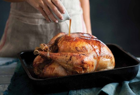 A woman pouring maple syrup over a maple glazed turkey in a black roasting pan.