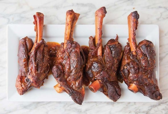 Four lamb shanks with coffee and ancho chile on a rectangular white plate on a white and grey marble surface.
