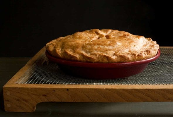An apple pie with Cheddar crust in a red pie pan on a cooking rack