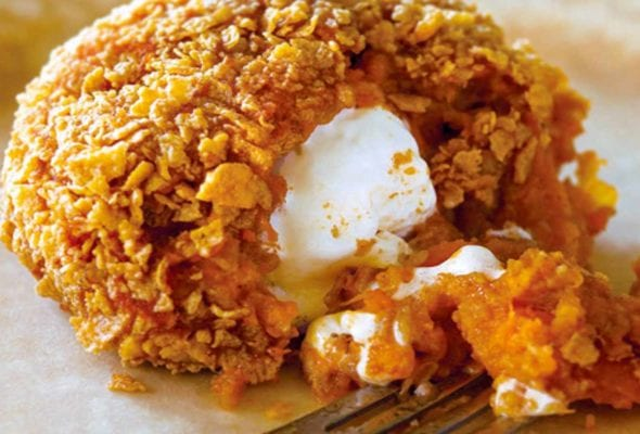 An inside-out sweet potato coated in corn flakes, with a marshmallow center.