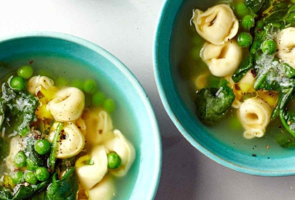 Two bowls filled with tortellini, peas, and spinach.