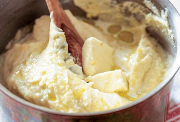 A pot of velvet mashed potatoes--made with plenty of butter, cream--with a wooden spoon and pat of butter on top