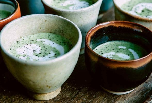 Four handmade bowls of green-speckled creamy broccoli soup with feta