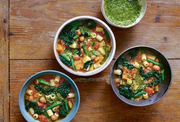 Three bowls of minestrone soup and a small bowl of pesto.