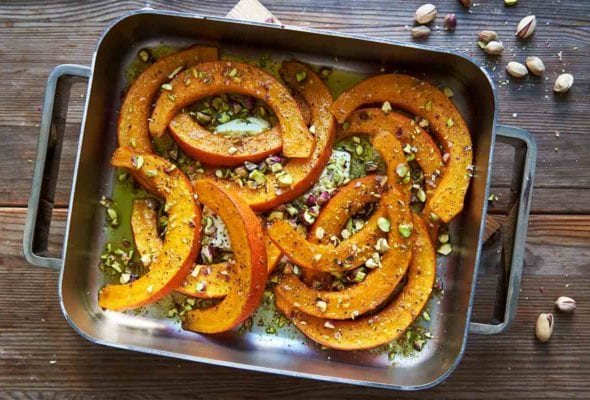 A metal roasting pan filled with roast butternut squash, feta, and pistachios on a wooden table with pistachios scattered around it.