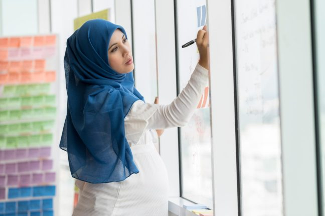 Businesswoman in hijab writes ides on adhesive notes on office window