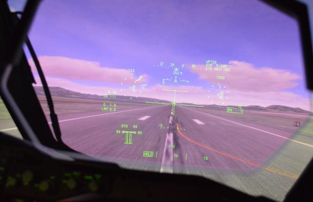 C2の操縦席正面にあるHUD。透明な画面に緑の表示で、機体の姿勢や方位、高度、速度、加速度がまとめて現れる=1月30日午後、航空自衛隊美保基地のC2飛行シミュレーター内で