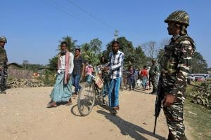 Villagers walk past Central Reserve Police Force (CRPF) personnel patrolling a road ahead of the publication of the first draft of the National Register of Citizens (NRC) in the Juria village of Nagaon district in Assam, on December 28, 2017. Credit: Reuters