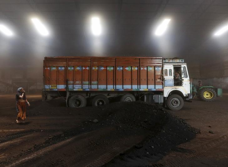 A worker speaks with the driver after unloading coal from a supply truck at a yard on the outskirts of the western Indian city of Ahmedabad April 15, 2015. Credit: Reuters/Amit Dave