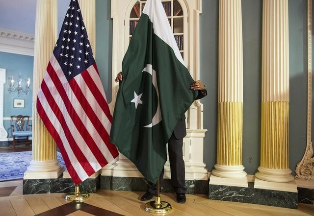 A State Department contractor adjust a Pakistan national flag before a meeting between U.S. Secretary of State John Kerry and Pakistan's Interior Minister Chaudhry Nisar Ali Khan on the sidelines of the White House Summit on Countering Violent Extremism at the State Department in Washington February 19, 2015. Credit: Reuters/Joshua Roberts/Files