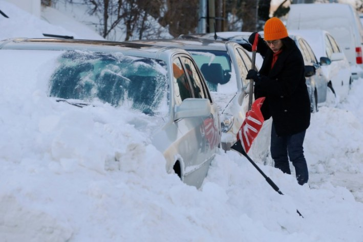 A woman digs out her car following winter snow storm Grayson in Boston, Massachusetts, US, January 5, 2018. Credit: Reuters/Brian Snyder