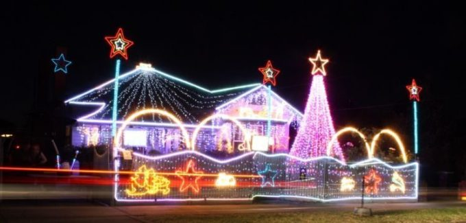 A home adorned with a Christmas light display with multi-coloured lights and large LED Christmas tree at the front.