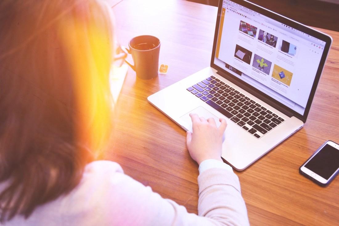 Frau sitzt lesend am Mac Book.