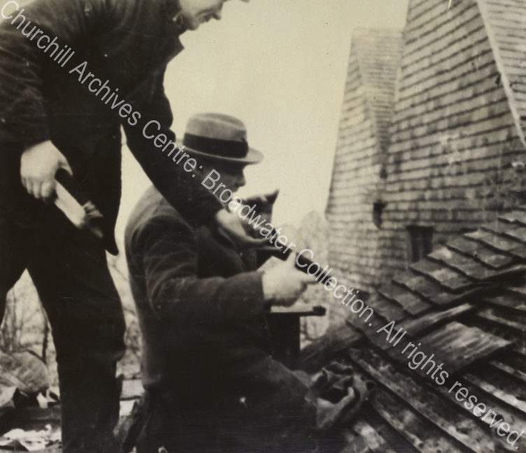 Photo shows WSC kneeling on the roof [at Chartwell] being handed a roof tile by a workman. WSC lifts a cigar to his mouth.