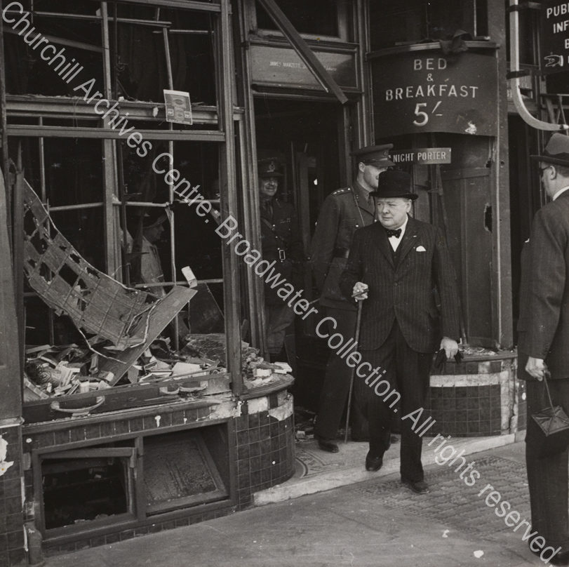 """WSC is shown walking out of a bomb-damaged building. A sign behind him reads """"Bed & Breakfast 5/""""."""
