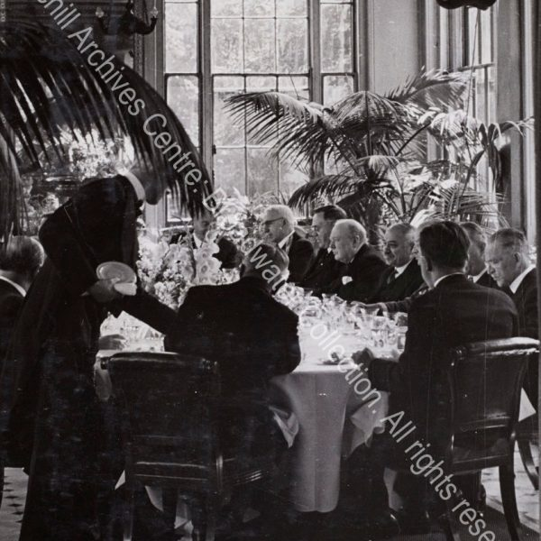Photo shows a formal gathering [Allied ambassadors' lunch at the Soviet embassy] seated at table amid large potted ferns. WSC is in the centre listening to talk at the table. Seated on his left is Ivan Maisky