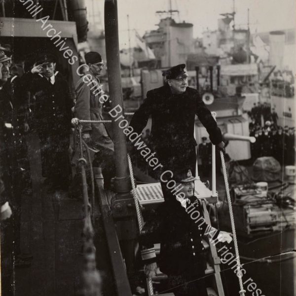 Photo shows WSC about to walking down the steps to leave a ship [?the Duke of York]. Admiral Sir Dudley Pound