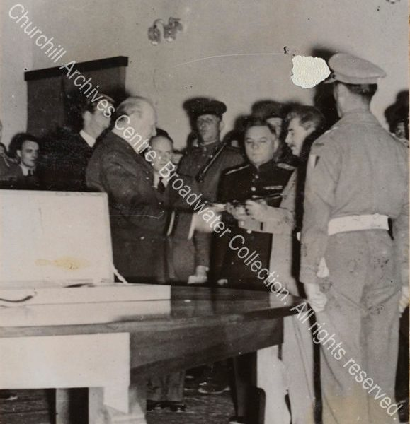 Photo shows WSC handing the sword to Stalin as a tribute at the Soviet Legation in Tehran [Iran]. Anthony Eden [later 1st Lord Avon] is just seen behind WSC and they are watched by a group of people.