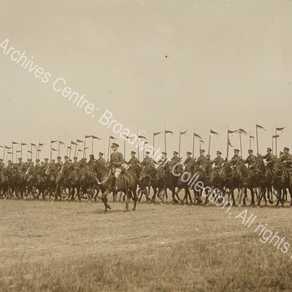 Photograph of a line of cavalry moving forward across open grassland [near Cologne