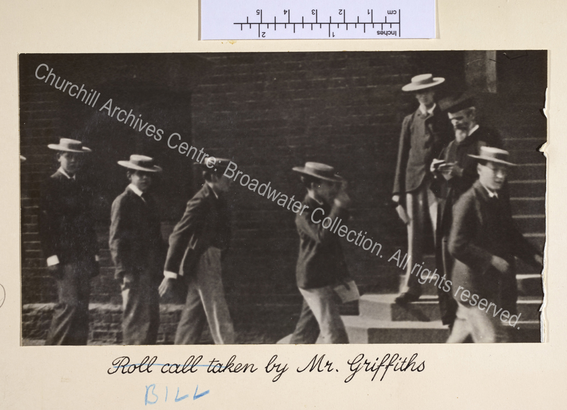 "Photograph shows Harrow schoolboys wearing straw boaters filing past a school master wearing a gown and mortar board. Note that caption originally read ""Roll call taken by"" and has been corrected."