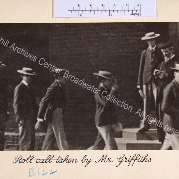 """Photograph shows Harrow schoolboys wearing straw boaters filing past a school master wearing a gown and mortar board. Note that caption originally read """"Roll call taken by"""" and has been corrected."""