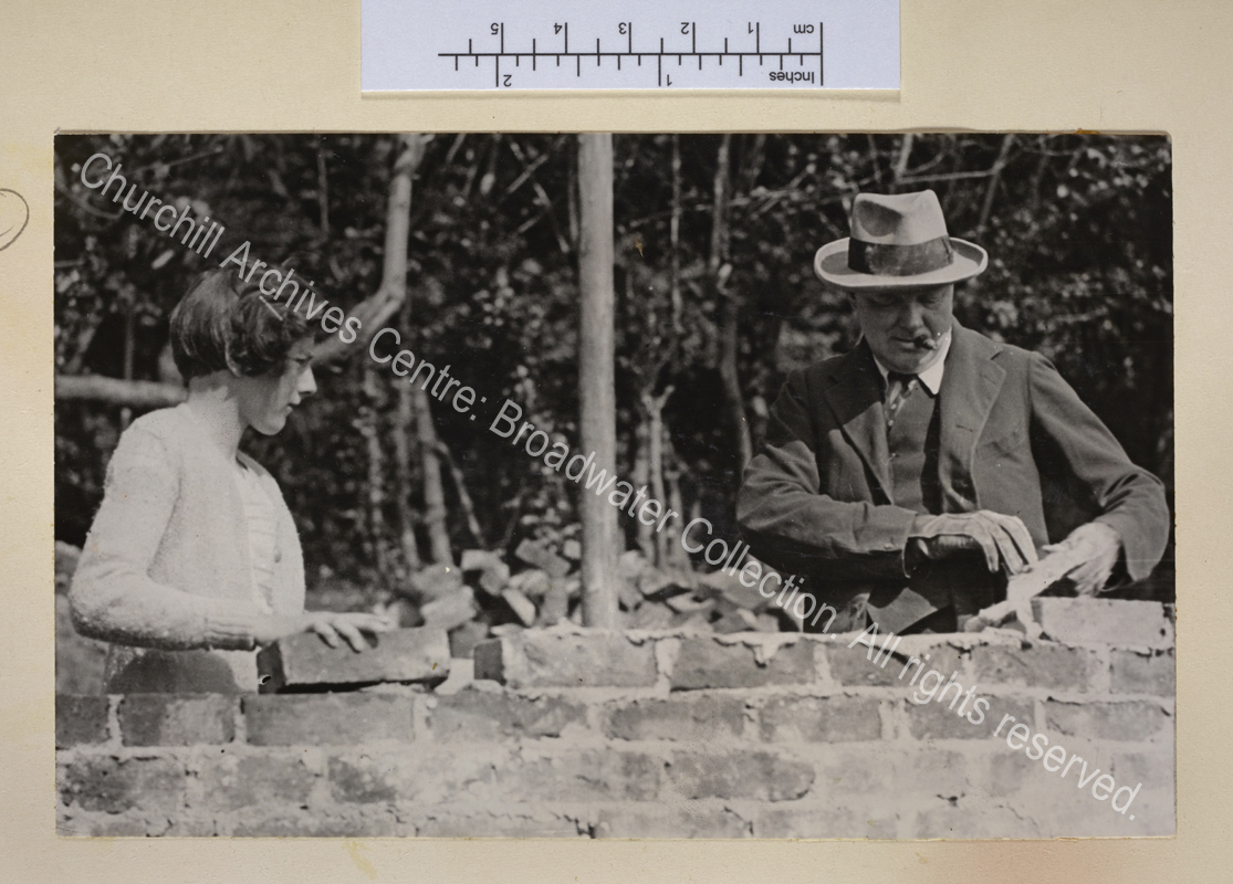 Photo of WSC (cigar in mouth) bricklaying at Chartwell with Sarah [Churchill