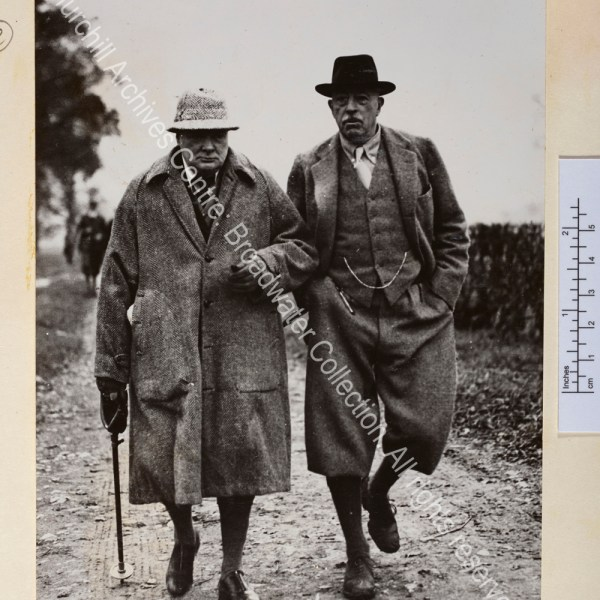 Photo shows WSC wearing tweed overcoat and hat