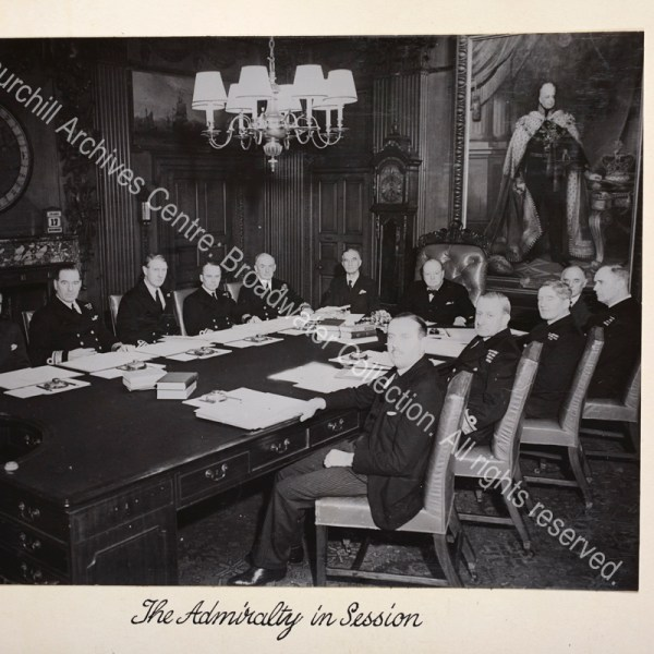 Photo showing WSC at the head of a large meeting table. Admiralty staff and officers flank the table with meeting papers and blotters in front of them.