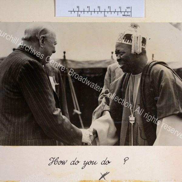 Photo shows WSC shaking hands with the Oni of Ife. The Oni of Ife is wearing traditional dress and a members' badge for the Kent County Agricultural Show.