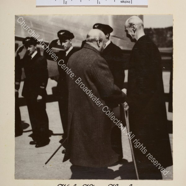 Photo shows WSC meeting King Haakon. Both are facing away from the camera. In the background there is an aeroplane and a line of men in uniform.