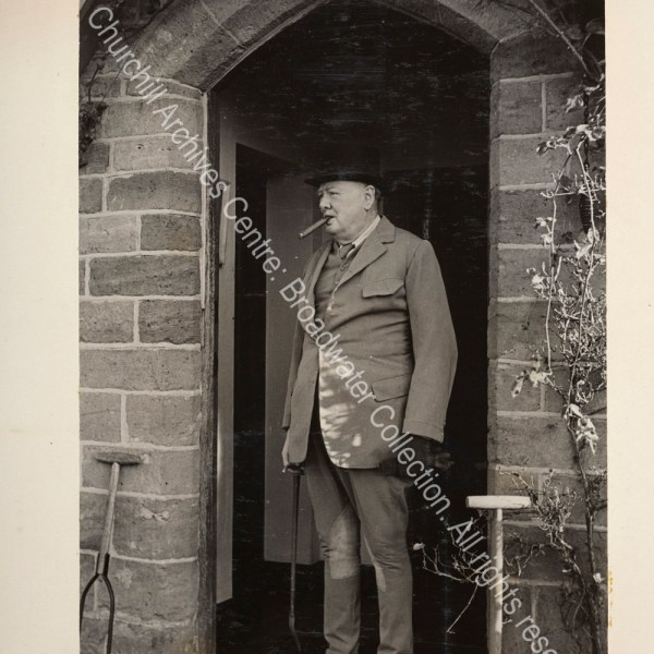 Photo shows WSC standing in a doorway wearing riding clothes and carrying a riding crop. [The occasion was WSC joining the Surrey and Burstow hunt to celebrate his 74th birthday].