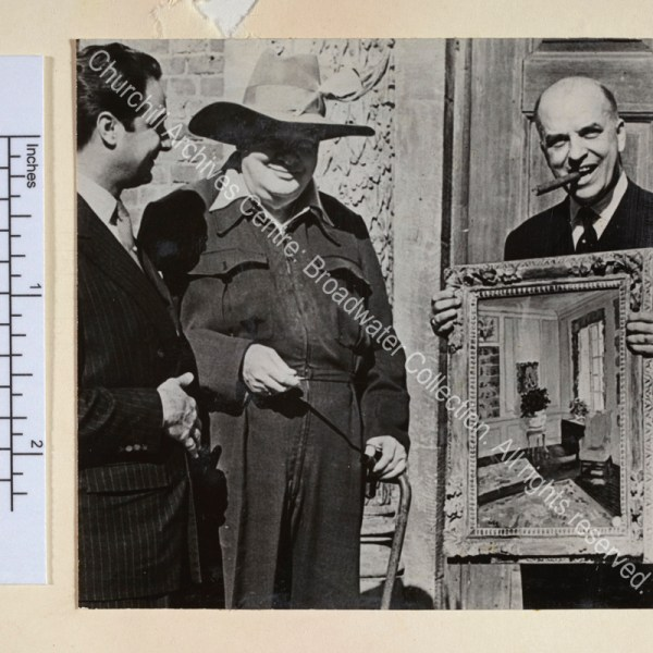 "Photo shows WSC at the Chartwell entrance wearing a siren suit and a broad-brimmed sombrero hat with a feather in it. He is presenting his painting ""The Blue Room"