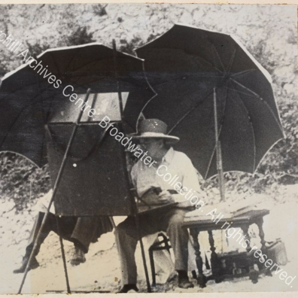 Photo shows WSC seated at a large easel absorbed in painting. He is wearing spectacles and a wide-brimmed hat and is shaded by two large umbrellas.