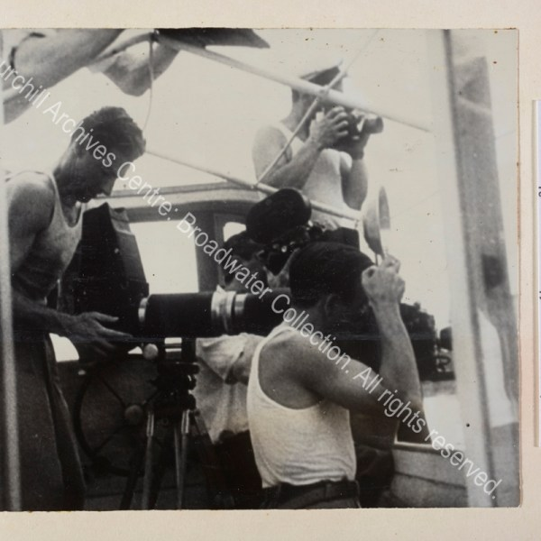 Photograph of a group of male press photographers in vests on board a boat. They are presumably photographing WSC while he paints.