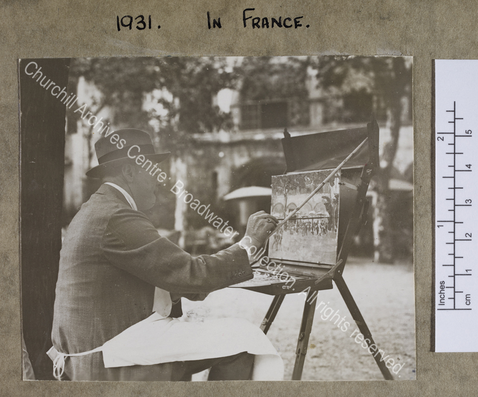 Three quarter length photograph of WSC painting [at St Jean de Luz].  He is sitting under a tree