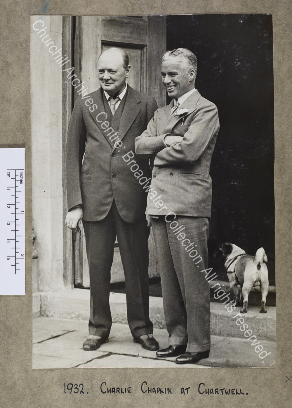Full length photograph of WSC standing with Chaplin in the doorway at Chartwell [Kent].  They are both smiling and looking to the left