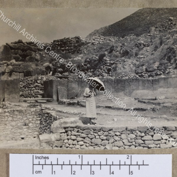 Photograph of CSC [while on a cruise of the Eastern Mediterranean on 1st Lord Moyne's yacht the Rosaura].  She is standing in the middle distance amid the walls of a ruined [?] classical site