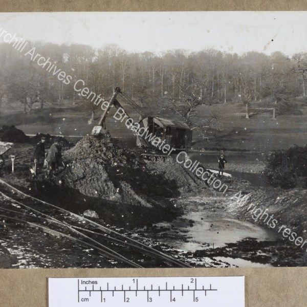 Photograph of a mechanical excavator and workmen digging in the drained lower lake at Chartwell [Kent]