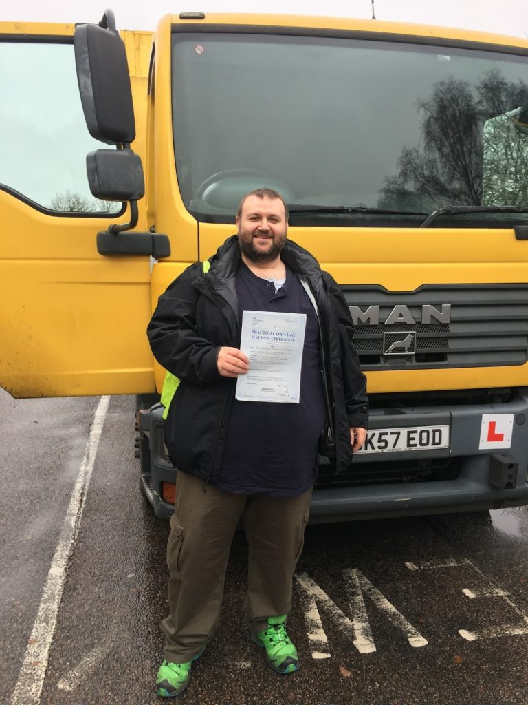 George standing in front of the HGV he trained in, holding his driving test pass certificate