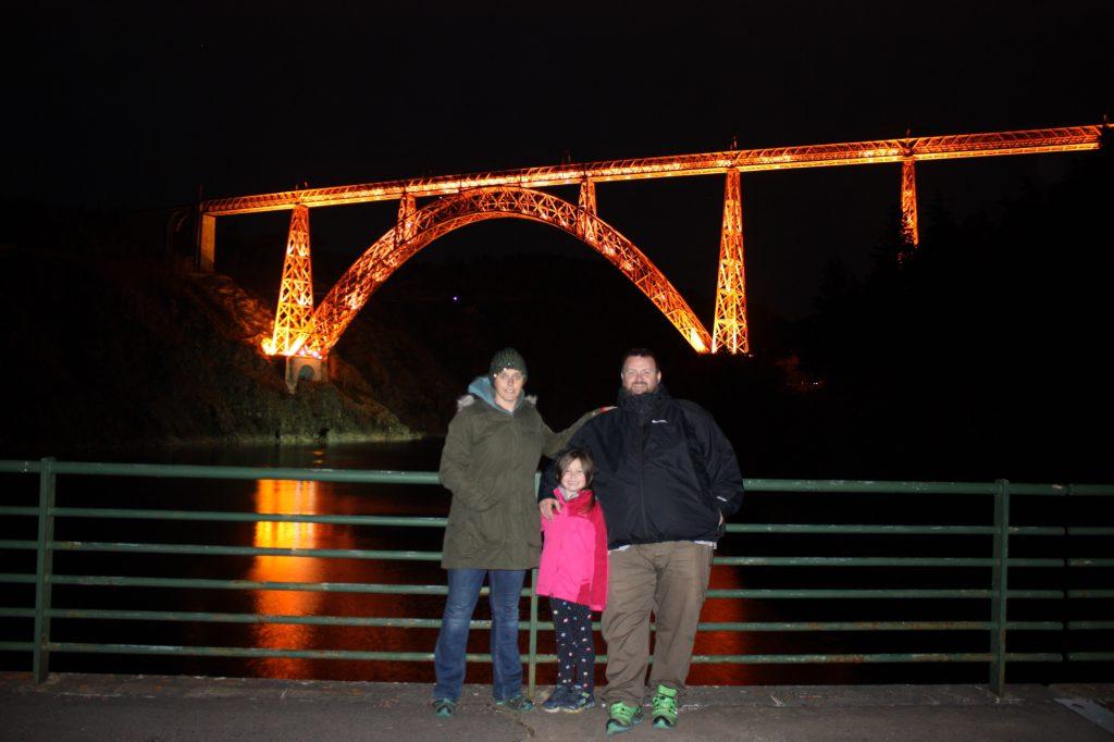 Karen, Olivia and George in front of the lit up Garabit viaduct