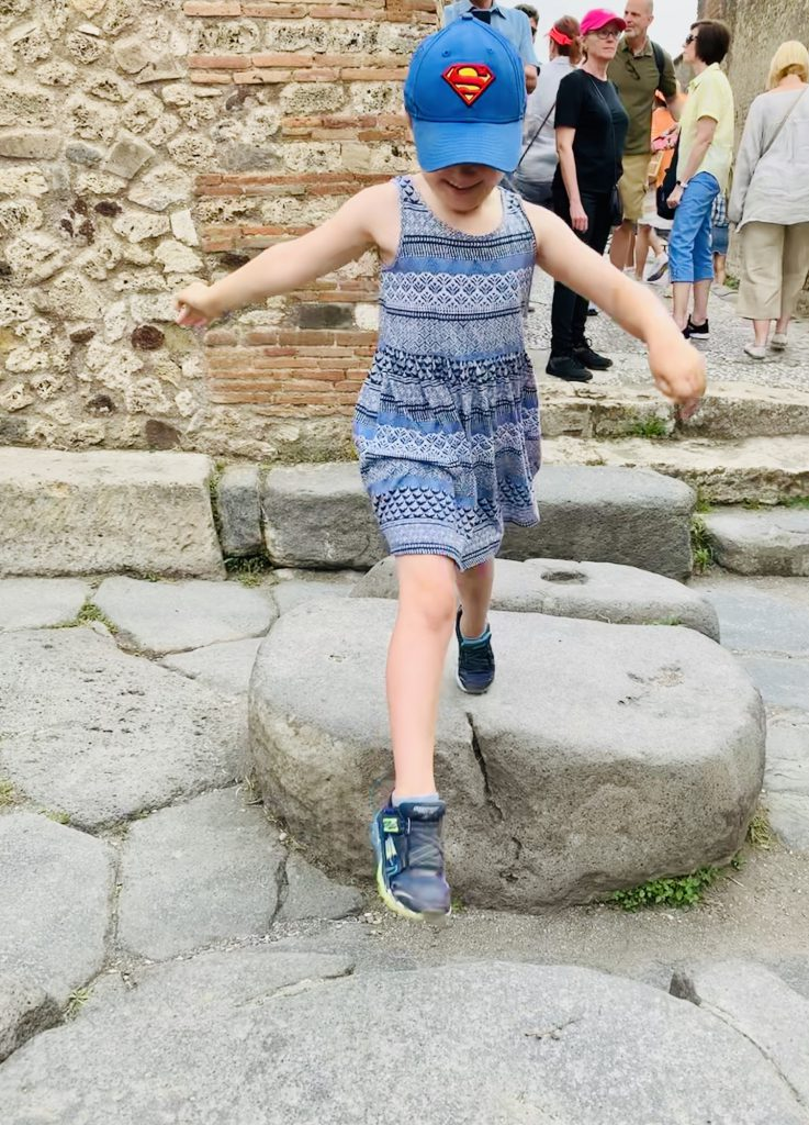Olivia using one of the raised zebra crossings in Pompeii