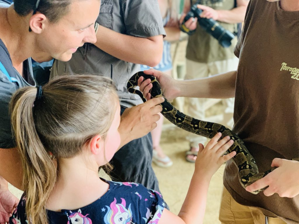 Karen and Olivia touching a snake at Touroparc Zoo