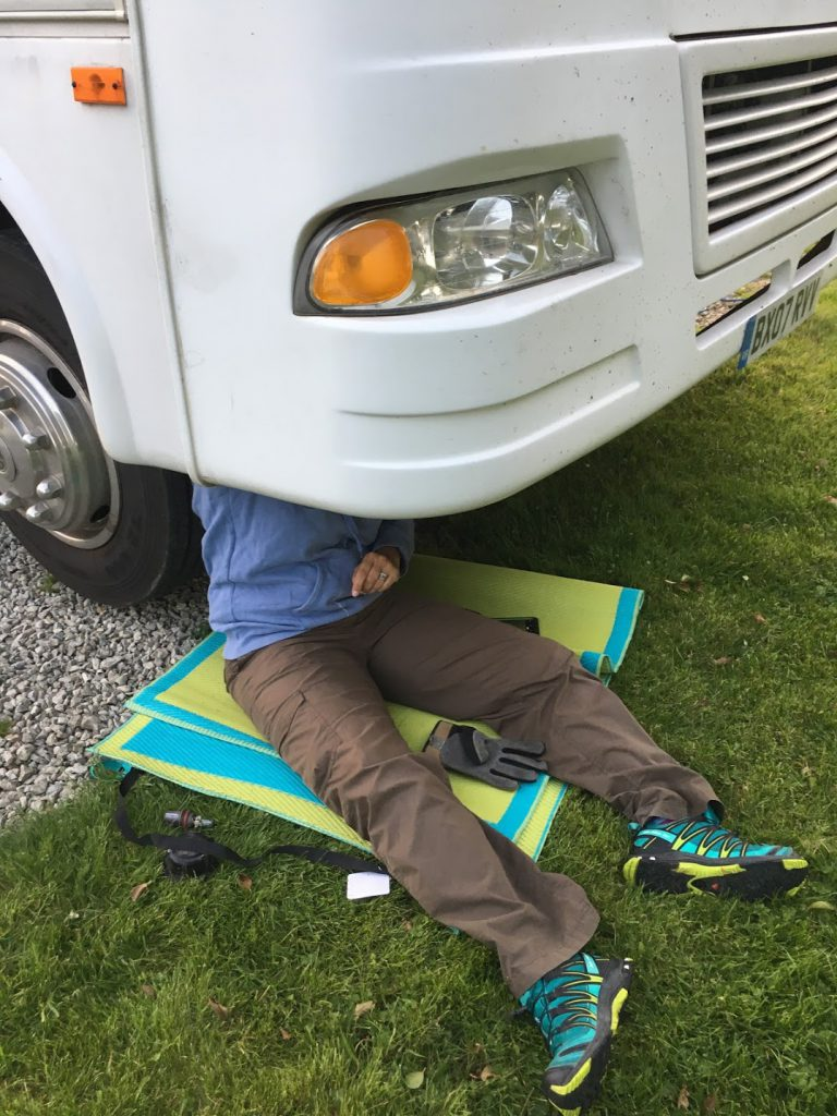 Karen sits under the front of the RV changing the headlight bulbs