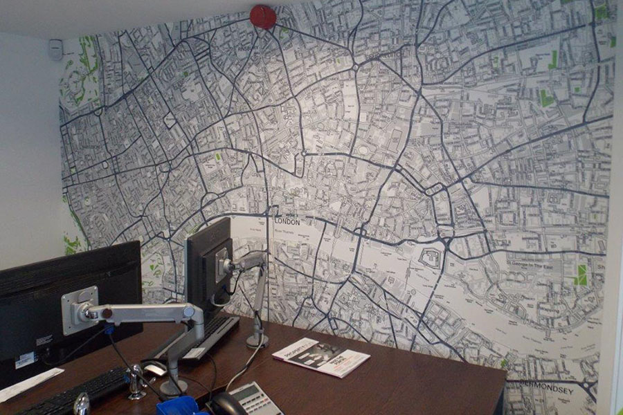Custom map wallpaper in an office with desk and computer monitors