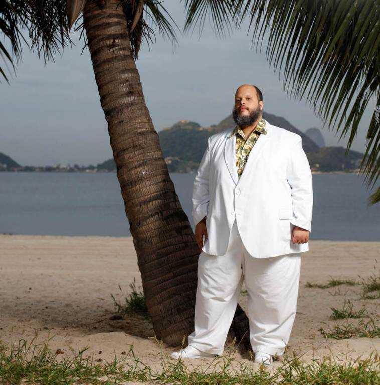 Ed Motta: Árdego e ganjento com terno branco na praia