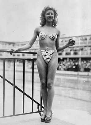 The new 'Bikini' swimming costume (in a newsprint-patterned fabric), which caused a sensation at a beauty contest at the Molitor swimming pool in Paris. Designer Louis Reard was unable to find a 'respectable' model for his costume and the job of displaying it went to 19-year-old Micheline Bernardini, a nude dancer from the Casino de Paris. She is holding a small box into which the entire costume can be packed. Celebrated as the first bikini, Luard's design came a few months after a similar two-piece design was produced by French designer Jacques Heim. (Photo by Keystone/Getty Images)