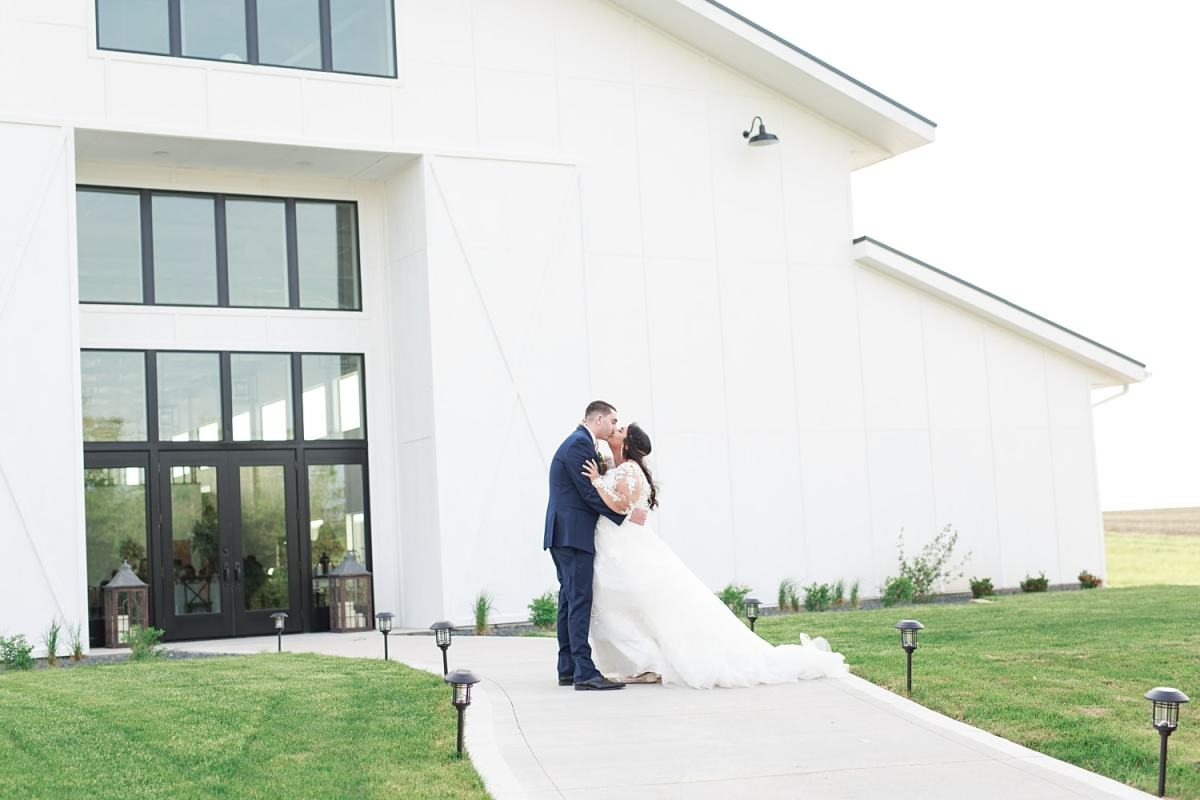 bride and groom kissing in front of emerald hills events