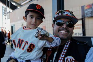 Alejandro Martinez, 6, and Enrique Alonso, 36, pose for a picture while they wait in line for autographs at AT&T Park on Feb. 11, 2017 .